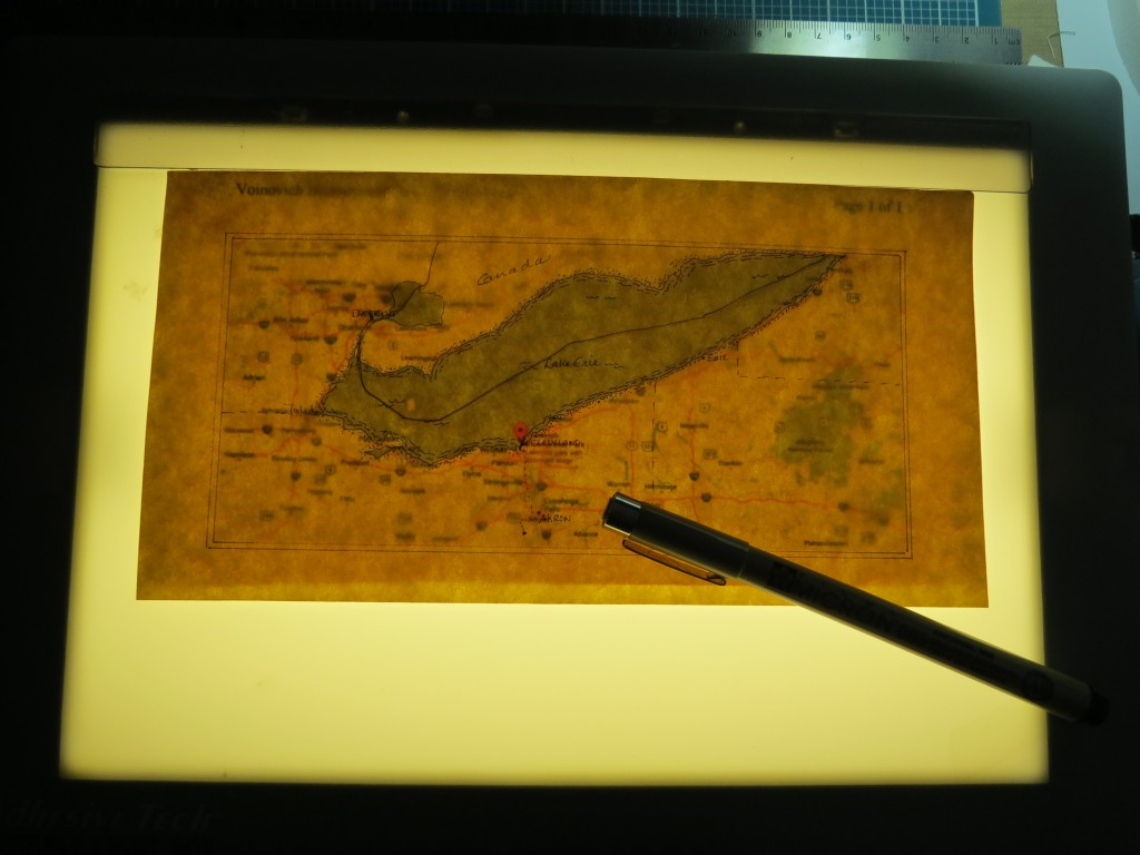 Scrapbook Pages Inspired by Treasure Island: parchment over printed map using light box for general outline.
