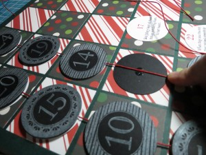 Countdown to Christmas: On the backside align the cording and use a glue dot to cove the cord and it will hold it in place.
