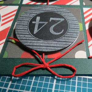 Countdown to Christmas: Bow secured with a glue dot place directly over the hole.