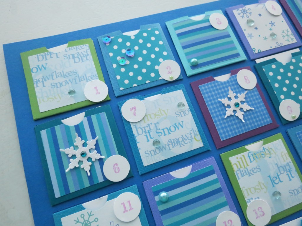 Countdown to Christmas: Decorating the fronts of the pockets with gems, glass pebbles, sequins, glitter paper snowflakes and pearls in a random fashion.