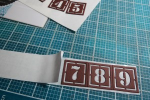 Great Expectations: Stencil Number Dies being placed on Stick It! Adhesive