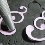 Embellishing Your Scrapbook Pages: Using embossing tool on backside of punched swirl to create dimension.