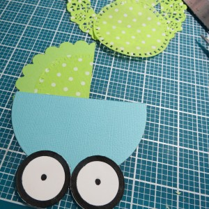 Baby Shower Scrapbook Ideas: Scored the canopy from the outside scallops, added a dotted doily for color and interest and attached wheels.