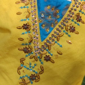 Detail shot of bead work on the outfit top.