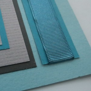 Ribbon ends are tucked to the back page by a slit along the tile edge.