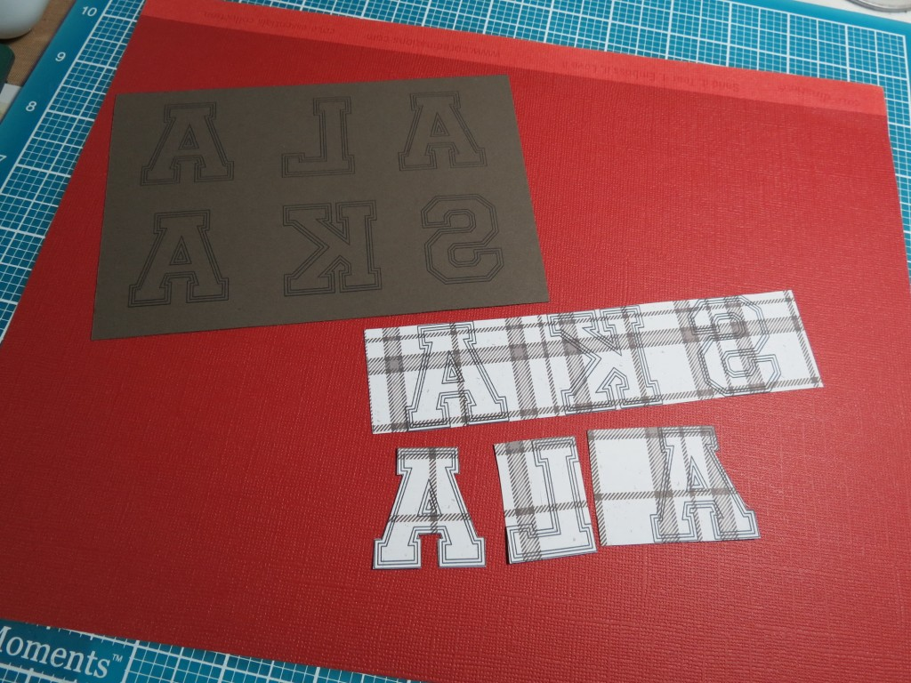 MM INSP Varsity letters on plaid, gray, and scarlet